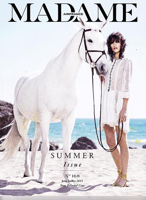 page de couverture magazine air france madame juillet 2015 - femme habillée avec une robe blanche qui tient un cheval blanc sur une plage