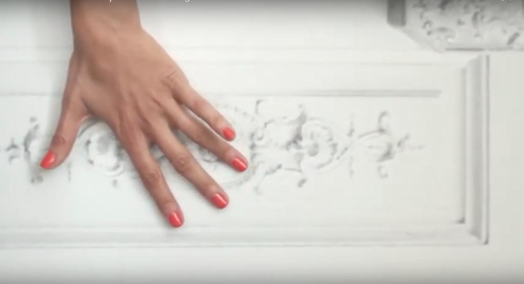main de femme avec vernis à ongle rouge coreil qui glisse sur un Mur blanc avec moulure à la maison champs elysées paris