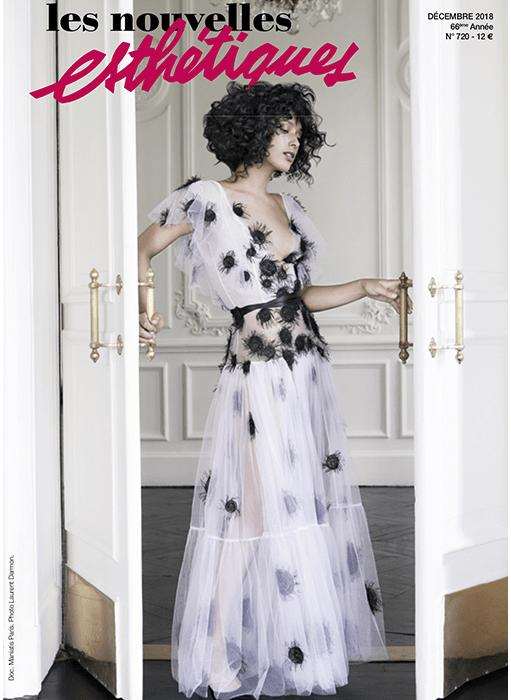 page de couverture magazine les nouvelles esthétique. femme avec robe blanche en tulle qui ouvre une porte avce des poignées dorées et des moulures