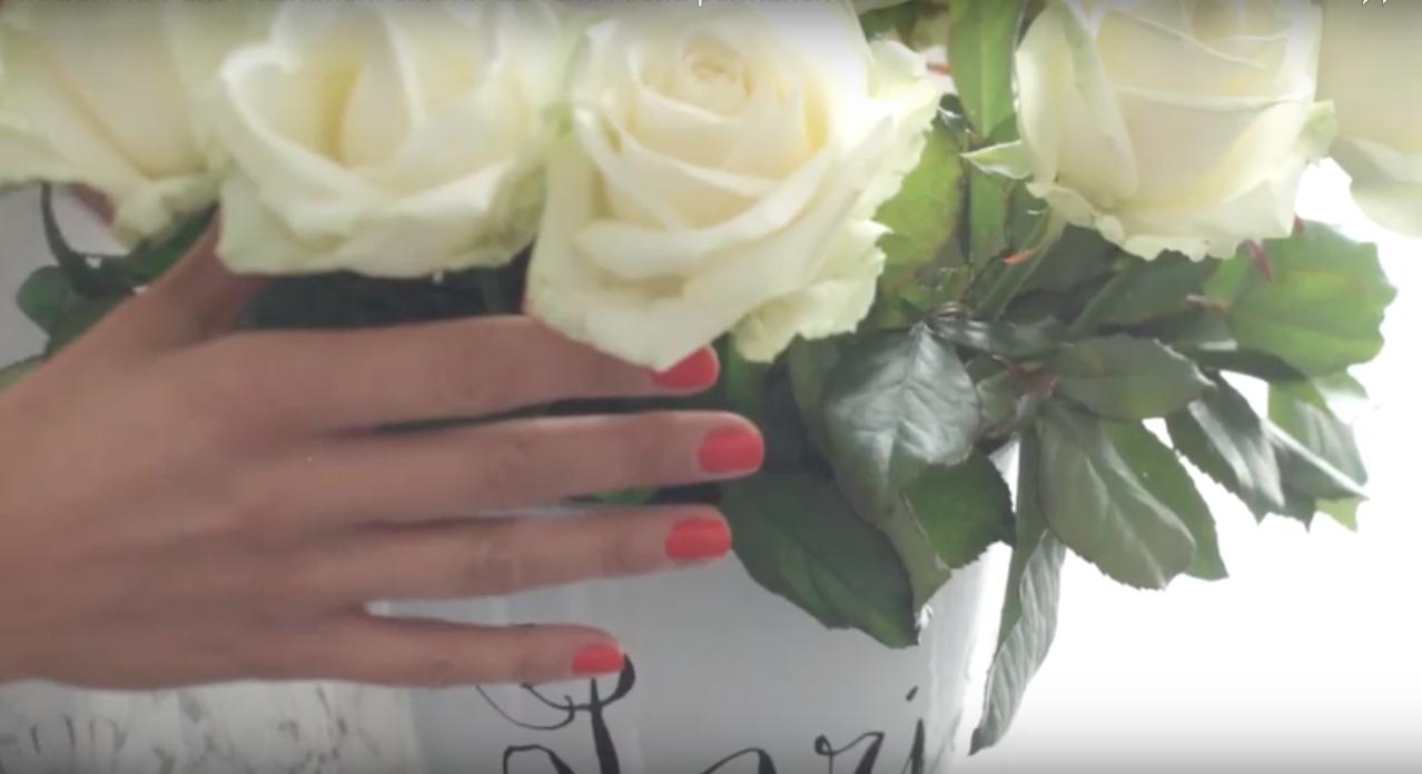 bouquet de rose blanche dans un vase Paris tenus par une main de femme avec vernis à ongle rouge corail